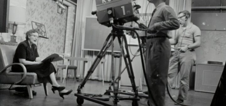 grayscale photography of man standing near studio camera and woman sitting while holding book